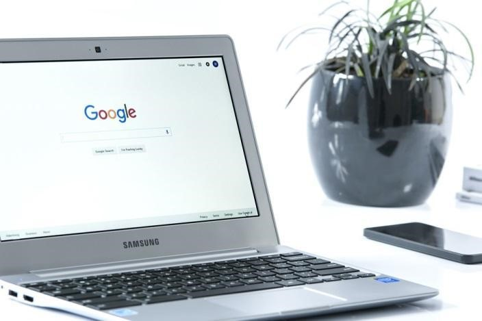 A silver laptop displaying Google's search engine page.
